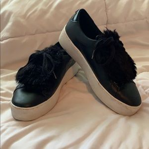 Black Michael Kors shoes with white sole and fur.